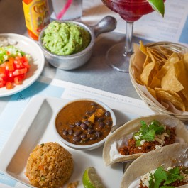 Table full of food: tacos, drinks and various sides