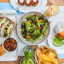 Table full of food: salad, tacos and various sides