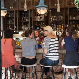 Four women sitting at the bar socializing